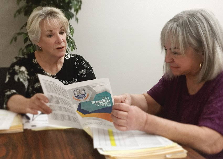 Elizabeth Barrett, Property Owners and Residents Association, 13815 Camino del Sol, adult learning coordinator goes over the upcoming education program with Pam Cherin.
