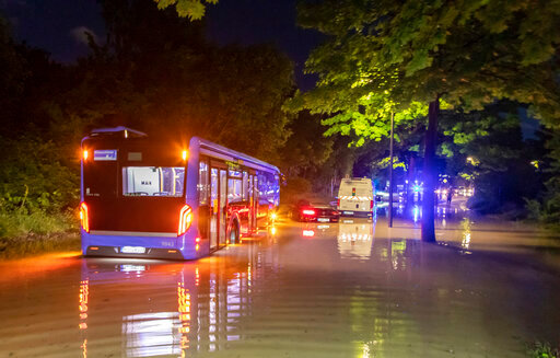 A bus stuck in water on a flooded road in Munich, Germany, Wednesday, June 23, 2021. In the evening, a storm had passed over Munich, which caused numerous fire brigade operations and flooded streets. (Andre Maerz/dpa via AP)