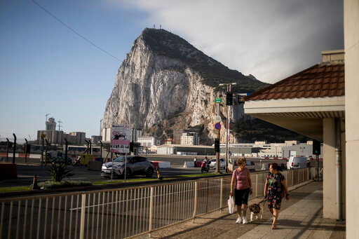 """Backdropped by the Gibraltar rock, people cross the Gibraltar airport runway, Thursday, June, 24, 2021. Gibraltar is holding a referendum on whether to introduce exceptions to the British territory's ban on abortion. Abortion is illegal in Gibraltar, unless it is needed to save the mother's life. Abortion is legally classified as """"child destruction"""" and is punishable by up to life in prison. (AP Photo/Javier Fergo)"""