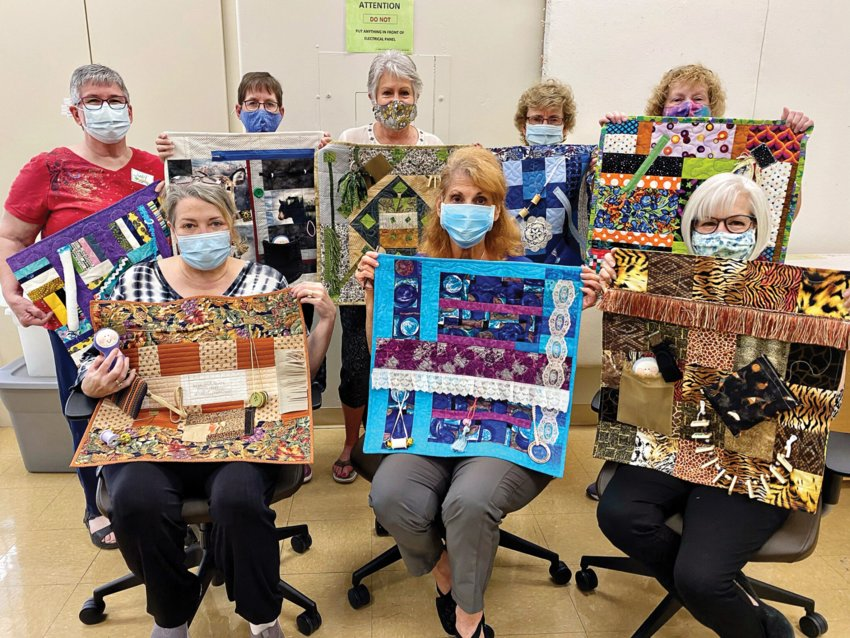 Members of the PebbleCreek Quilters show off the colorful sensory mats they created for Hospice of the Valley patients.