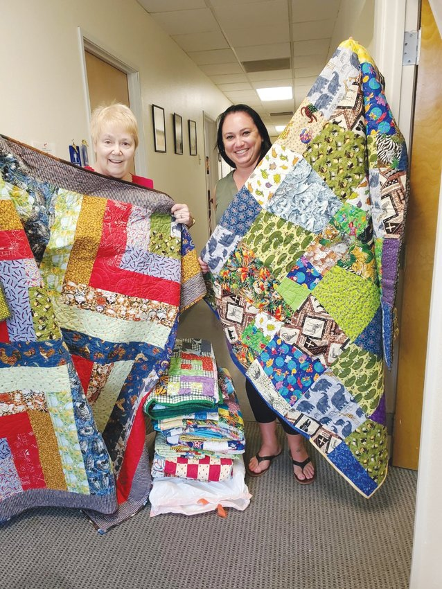 Shari Heath, left, of Friendship Quilters, Fabric Artists in Sun City, delivers 43 quilts to children at Family Support Resources in Phoenix, represented by Katie Vasquez. [Submitted photo]