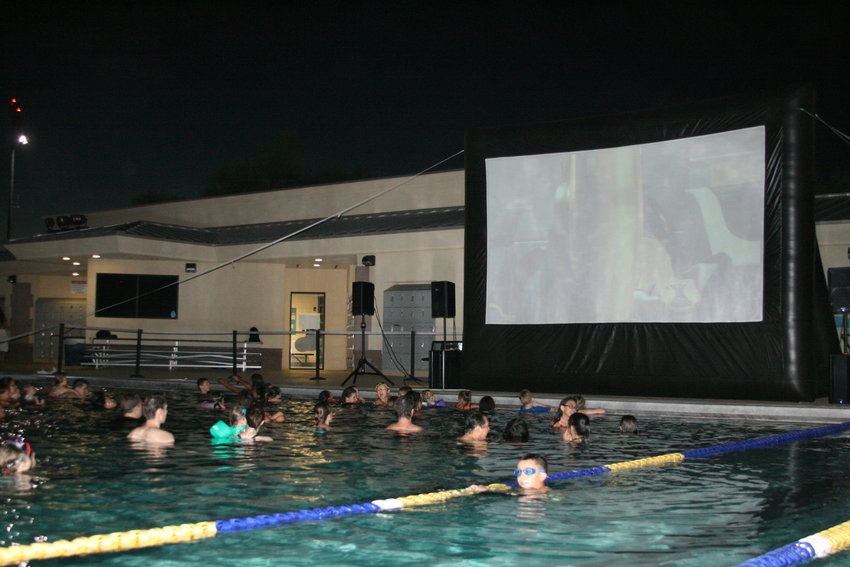 People watch a previous dive in movie while relaxing in the pool at the Surprise Aquatic Center.