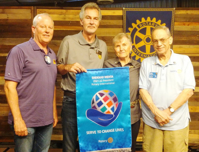 """Pictured, from left, outgoing Glendale Rotary Club President Ben Butler, Rotary District 5495; incoming Governor Brett McKeand; incoming Glendale Rotary Club President Nancy Germond; and District Assistant Governor Lou Rotundo, stand behind Rotary International's theme flag for 2021-2022, """"Serve to Change Lives."""""""
