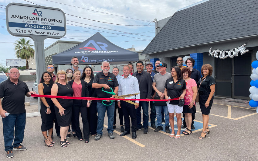 City officials join employees of American Roofing & Waterproofing to cut the ribbon on the company's new Glendale business.