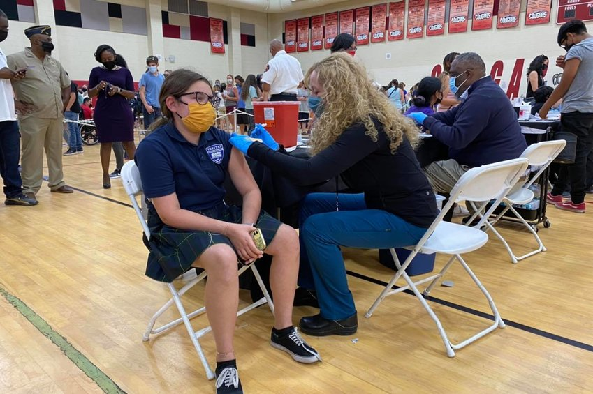 Dr. Cara Christ administers a COVID-19 vaccine in May to a student at the Roosevelt School District's C.O. Greenfield School in south Phoenix.