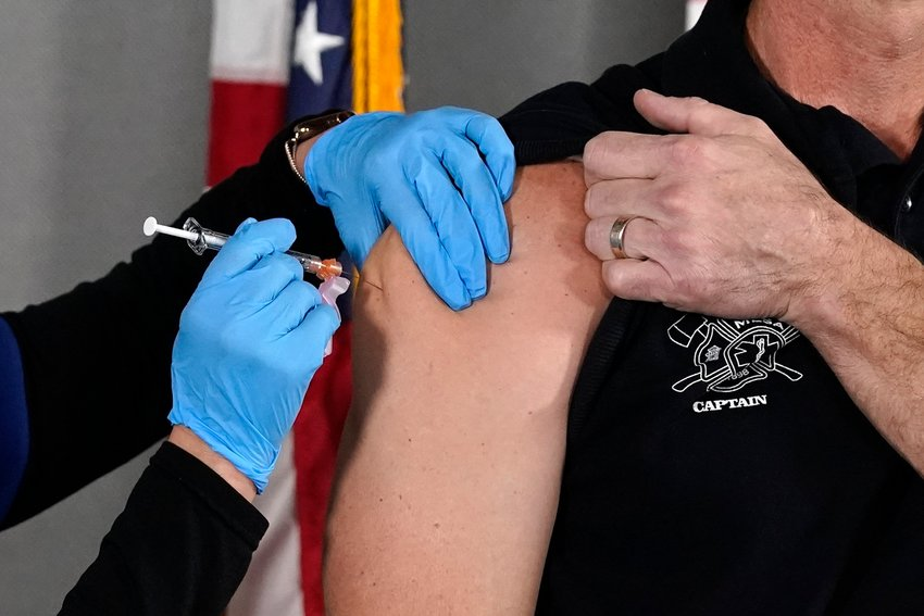 In this Wednesday, Dec. 16, 2020 file photo, the Pfizer vaccine for COVID-19 is administered at the Arizona Department of Health Services State Laboratory in Phoenix. ADHS reported approximately 1,479 additional COVID-19 cases and seven deaths on Friday, with more than 900 patients hospitalized around the state.