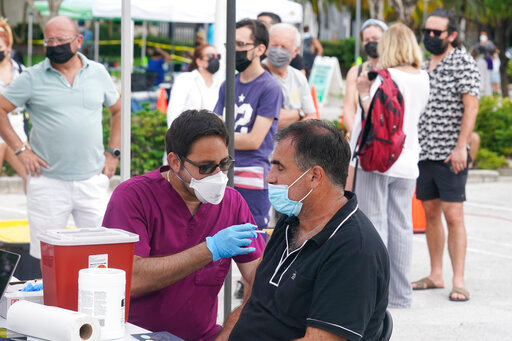 Carlos Anacleto closes his eyes as he receives the Pfizer COVID-19 vaccine from nurse Jorge Tase, as others wait their turn, Wednesday, Aug. 4, 2021, in Miami Beach, Fla. (AP Photo/Marta Lavandier)