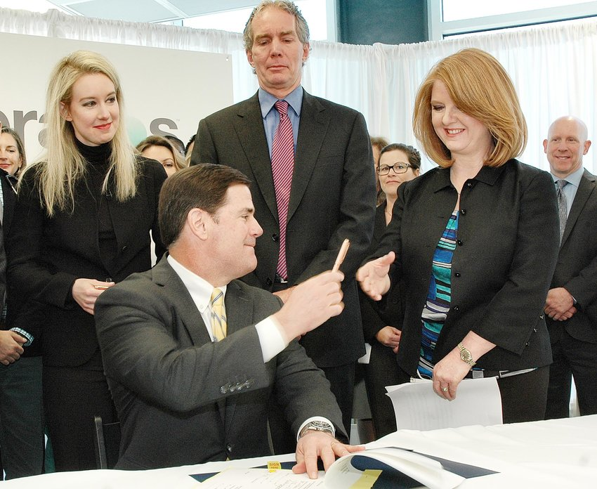 Gov. Doug Ducey signed legislation in 2015 to allow people to order their own blood tests. Elizabeth Holmes, founder of Theranos, who lobbied for the change, is at left.