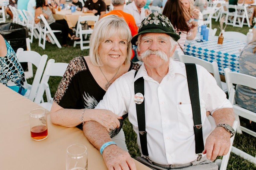 A couple dressed in German-inspired garb smile at the 2019 Oktoberfest celebration.