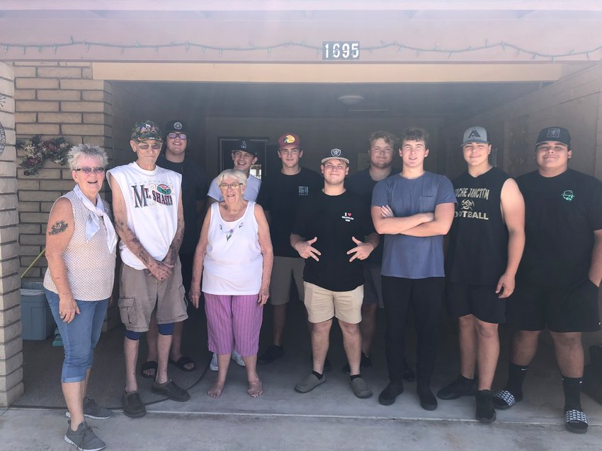 Players on the offensive and defensive lines on the Apache Junction High School varsity football team helped an elderly couple move their furnishings across the street to a new retirement community.