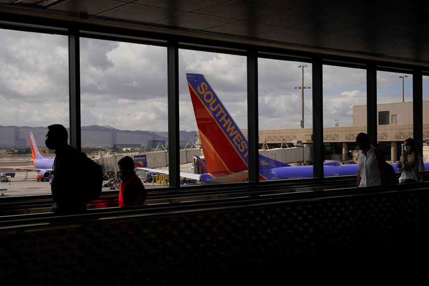 Passengers walk past a Southwest Airlines plane at Sky Harbor International Airport in Phoenix, Friday, March 26, 2021.
