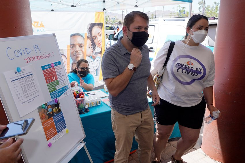 Rep. Ruben Gallego, D-Ariz., left, is joined by Kristin Urquiza, right, as they speak at a pop-up informational tent increasing efforts to bring more vaccine doses into Latino neighborhoods at a local shopping plaza Friday, May 7, 2021, in Phoenix. Gallego said he is helping organize vaccination events in Latino neighborhoods, including one May 15 at a west Phoenix high school. (AP Photo/Ross D. Franklin)