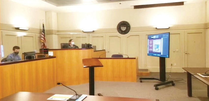 Judge Alisha Villa, second from left, sits at the bench in a Phoenix courtroom during a virtual traffic court hearing. The defendant will teleconference into the courtroom through the TV screen. [Submitted photo/City of Phoenix]