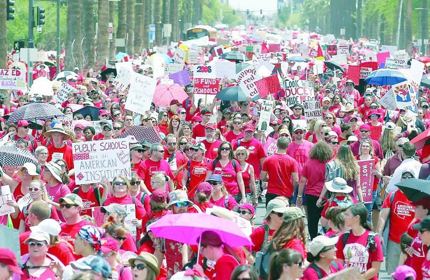 Arizona teachers and supporters protest on the street in Phoenix in 2018 during a teacher walkout. Gov. Doug Ducey, or whoever succeeds him, can't conduct a future financial raid on a school trust fund account without first getting congressional approval, a judge has ruled.