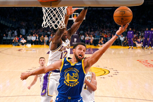 Golden State Warriors guard Stephen Curry, front, shoots as Los Angeles Lakers forward Devontae Cacok defends during the first half of a preseason NBA basketball game Monday, Oct. 14, 2019, in Los Angeles. (AP Photo/Mark J. Terrill)