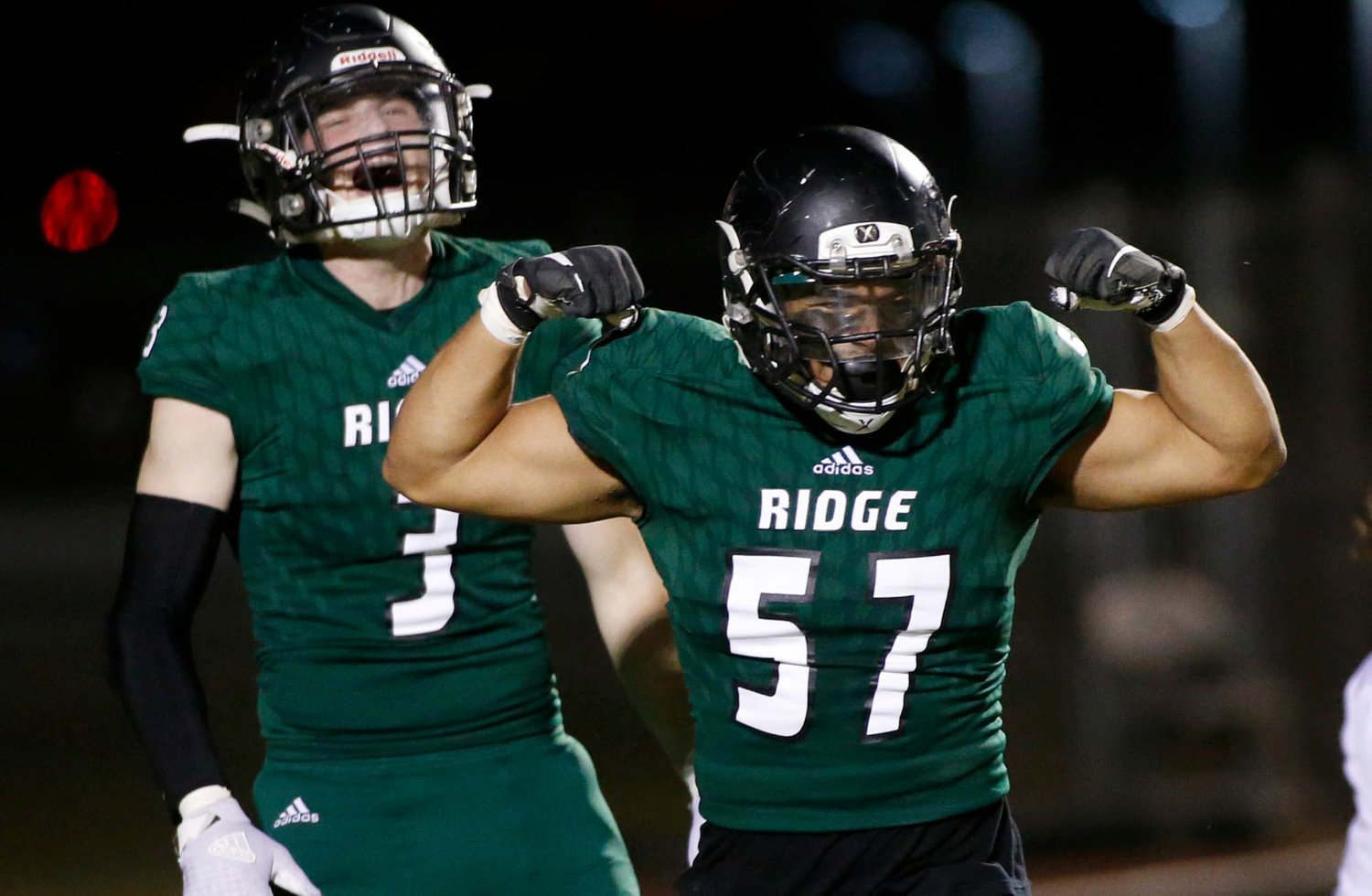 Mountain Ridge junior linebacker Derek Torres (57) flexes his muscle as he celebrates with teammate Jackson Rossi after a sack against Sandra Day O'Connor during the first half of their 6A football game on Friday, Nov. 1.