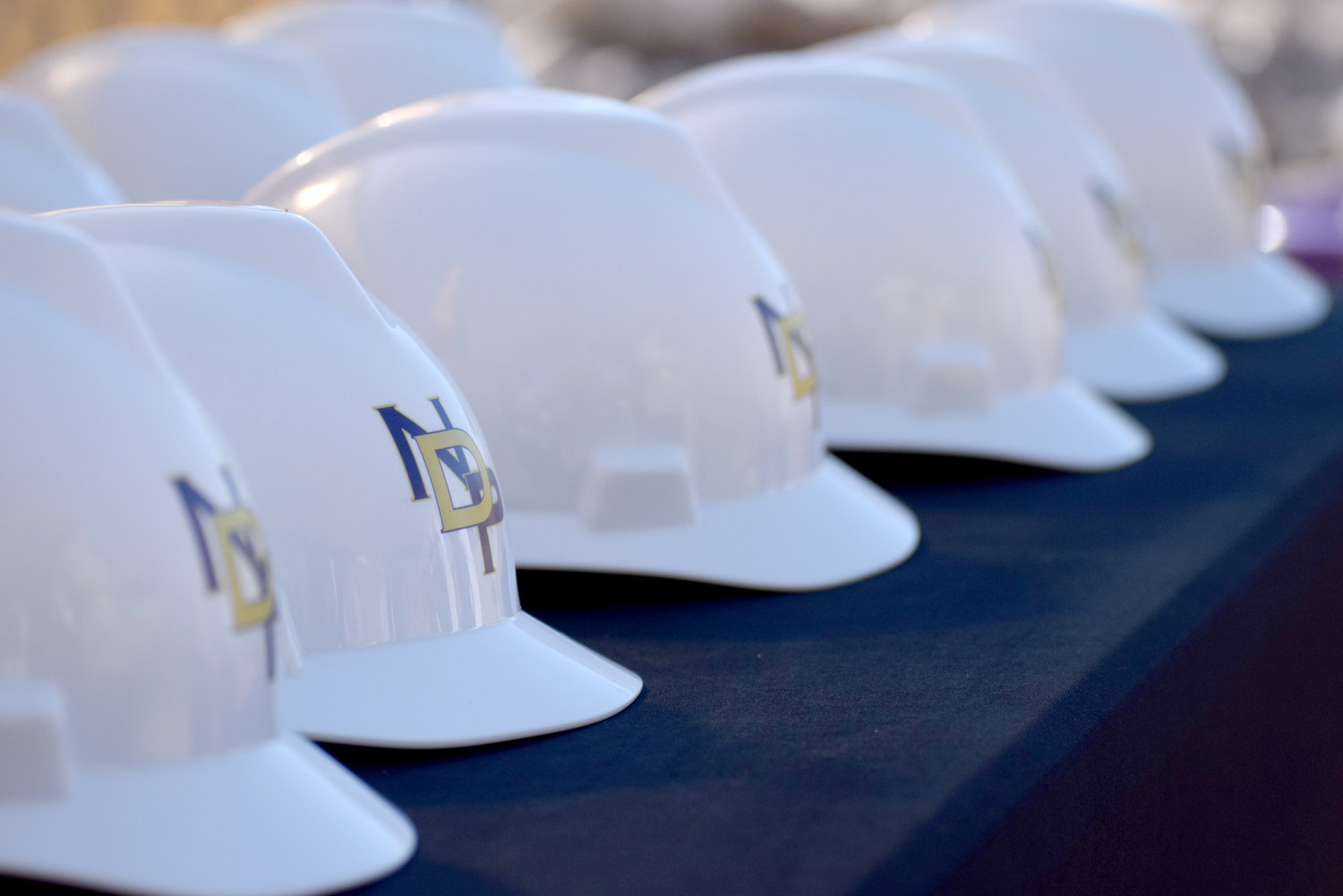 Hard hats line a table at Notre Dame Prep's groundbreaking for its new performing arts center.