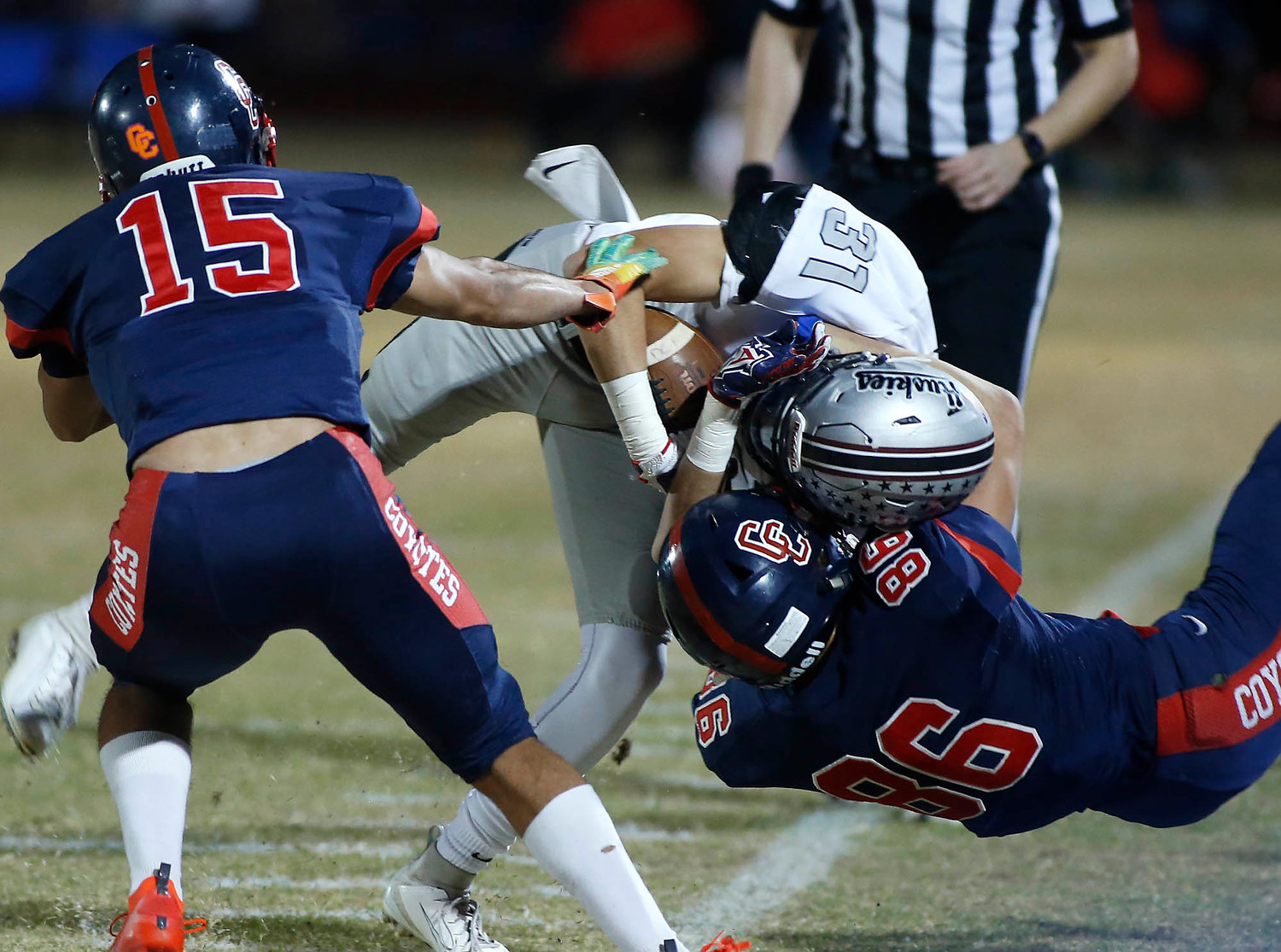 Centennial junior defensive end DJ Gleash (86) and senior cornerback Eric Haney (15) tackle Hamilton's Christian Anaya after a catch during the first half of their playoff football game on Friday.