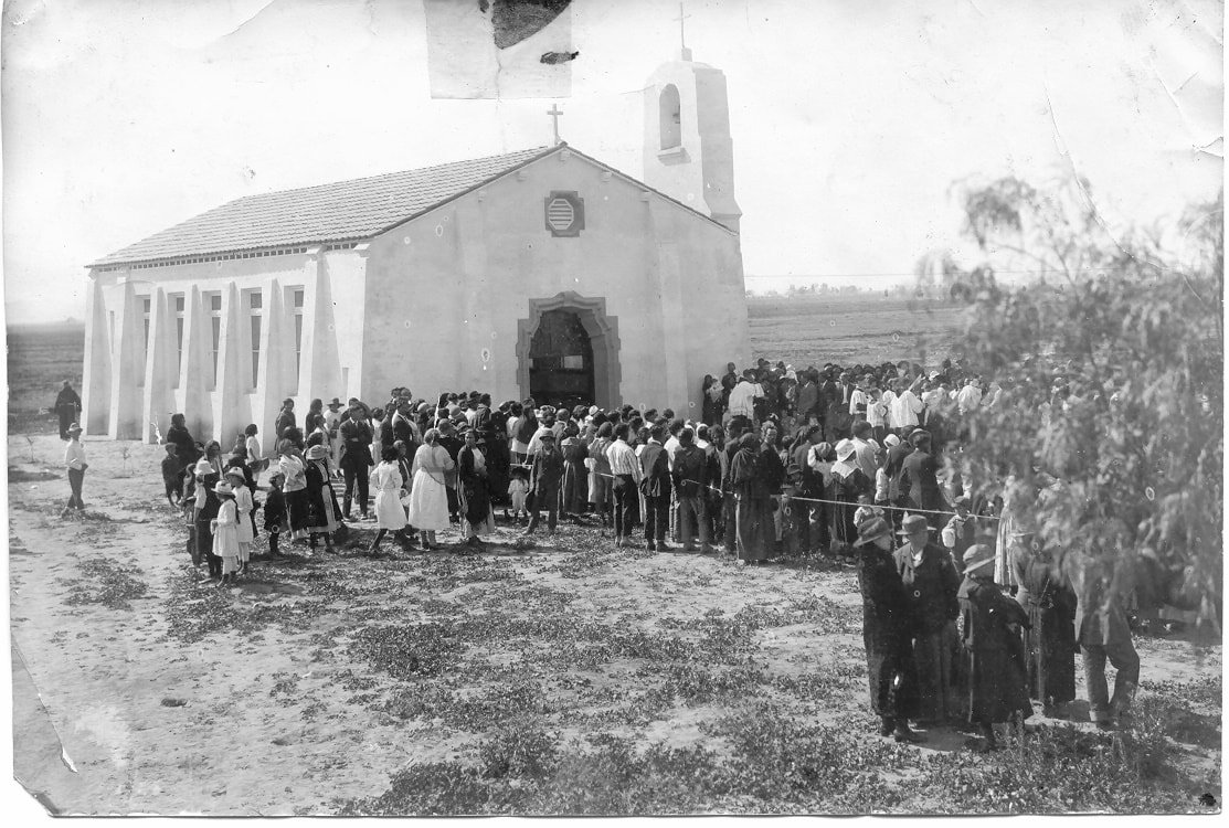 An early photo of parishioners attending the St. Thomas Aquinas Mission Church at the southwest corner of Neolin Avenue and Wigwam Boulevard. The church celebrated its 100th anniversary this month. In the 1970s, the church moved to a larger location near Thomas and Litchfield roads in Avondale. [Submitted photo]