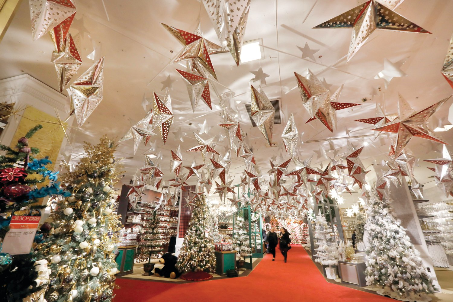 In this Nov. 5, 2019 file photo, shoppers browse the Holiday Lane section at the Macy's flagship store in New York. Experts predict another busy holiday shopping season.