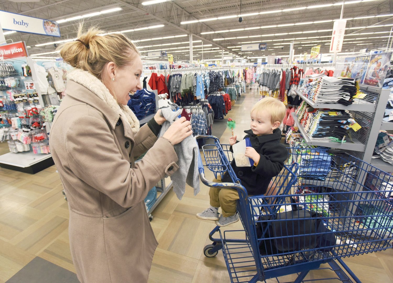 Karin Bader and two-year-old son Calvin, of Chicago, shop in the children's clothing section during Black Friday week at the Meijer store in Stevensville, Michigan.