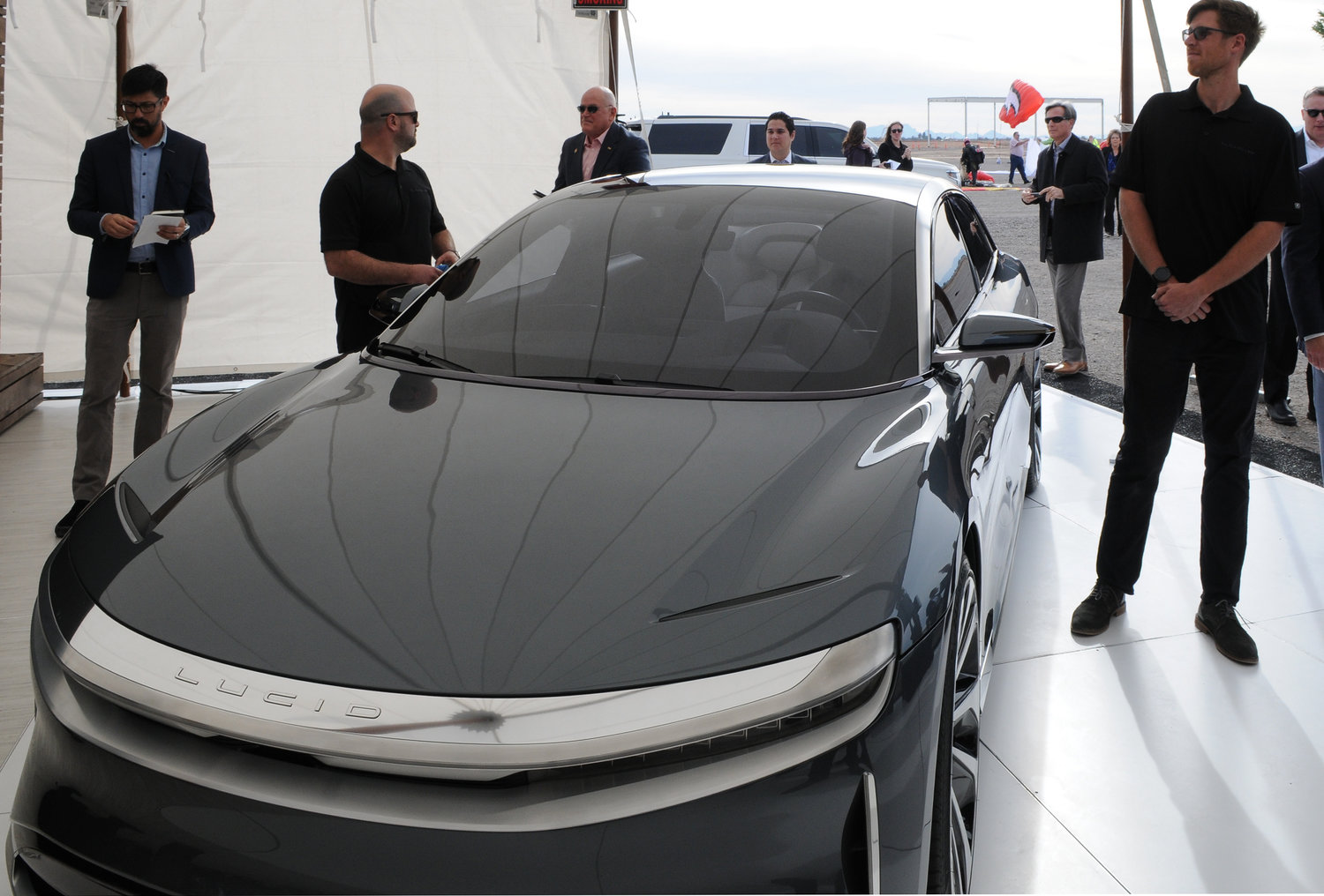 "Attendees at a ceremony Monday in Casa Grande look over what Lucid Motors says will be its first vehicle manufactured here with a price tag ""north of $100,000."""