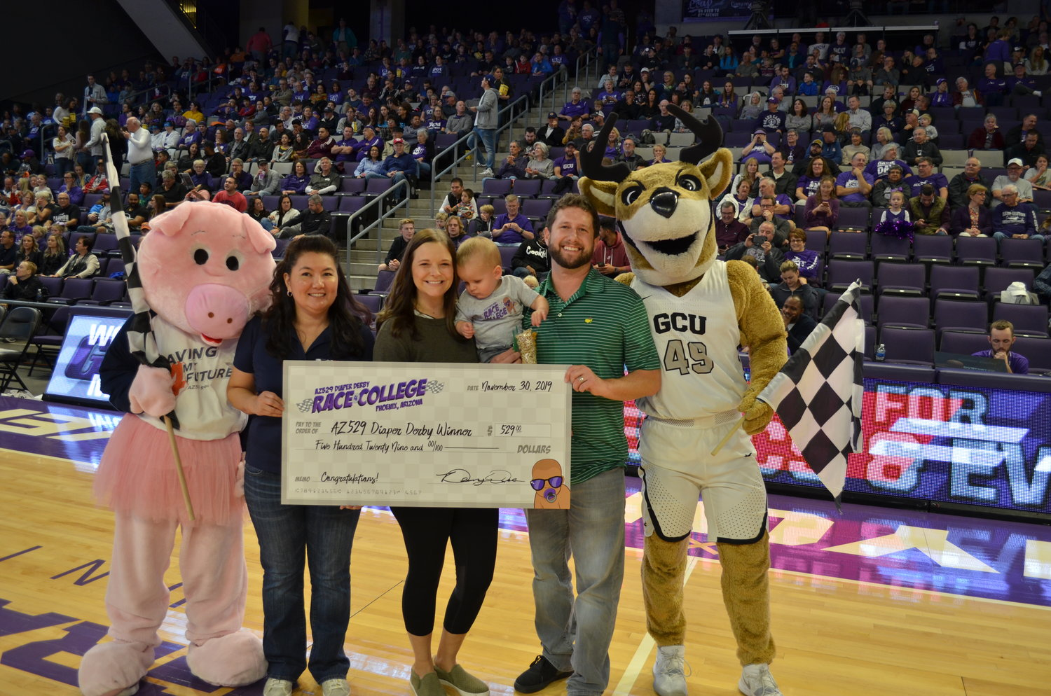 Jax and his family with the check for winning the diaper derby at Grand Canyon University.