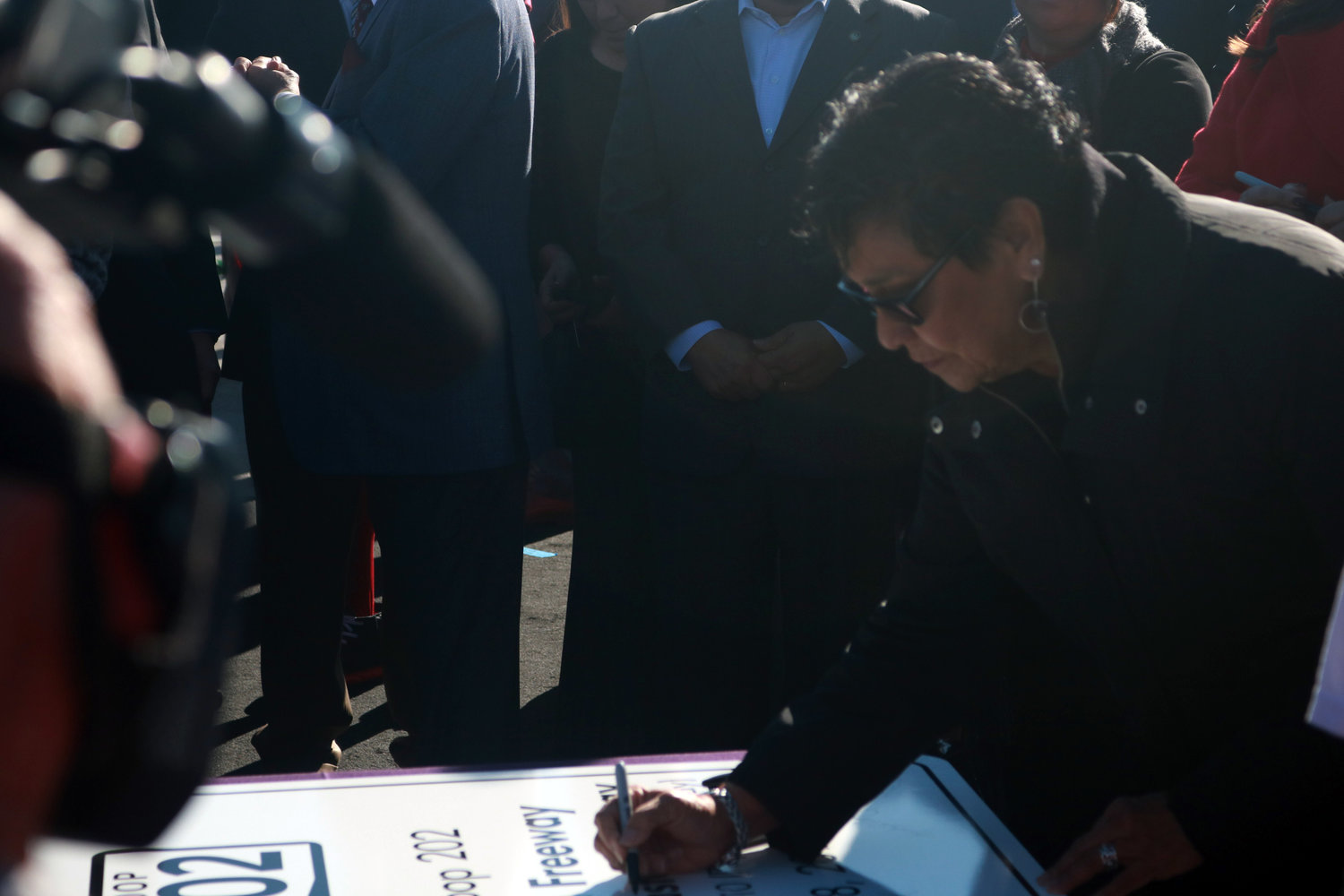 Verma Pastor, wife of late U.S. Congressman Ed Pastor, autographs a sign during the kickoff of the Loop 202 South Mountain Freeway.