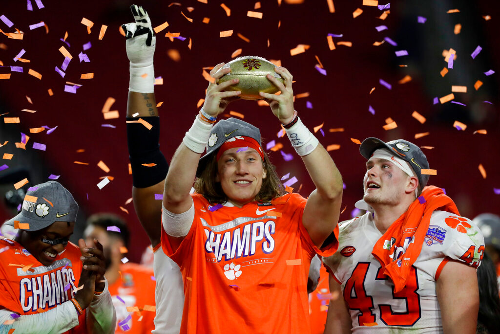 Clemson quarterback Trevor Lawrence holds up the trophy after Clemson's 29-23 win over Ohio State in the Fiesta Bowl College Football Playoff semifinal Saturday at State Farm Stadium in Glendale. [AP Photo/Rick Scuteri]
