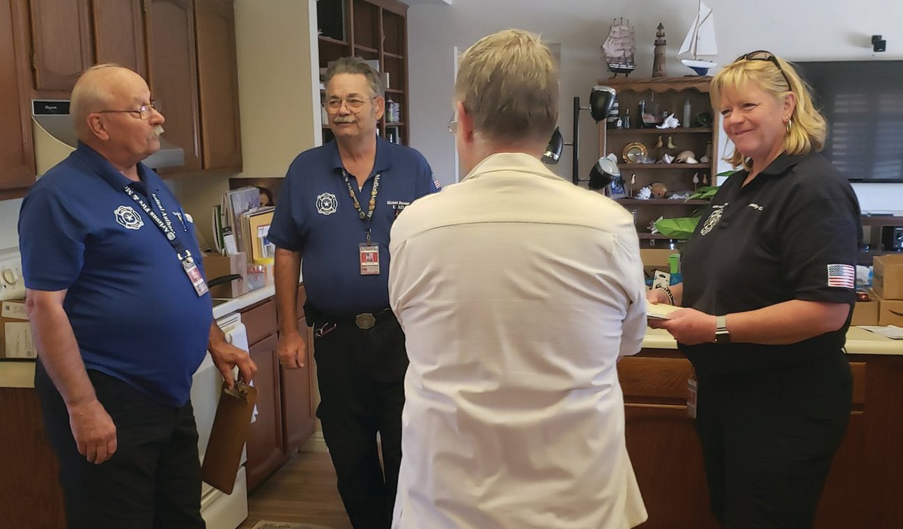 Arizona Fire & Medical Authority volunteers Doug Randall, left, and Michael Bannon, along with Kim Campbell, Assistant Fire Marshall, discuss fire safety issues with a Sun City West resident in his home