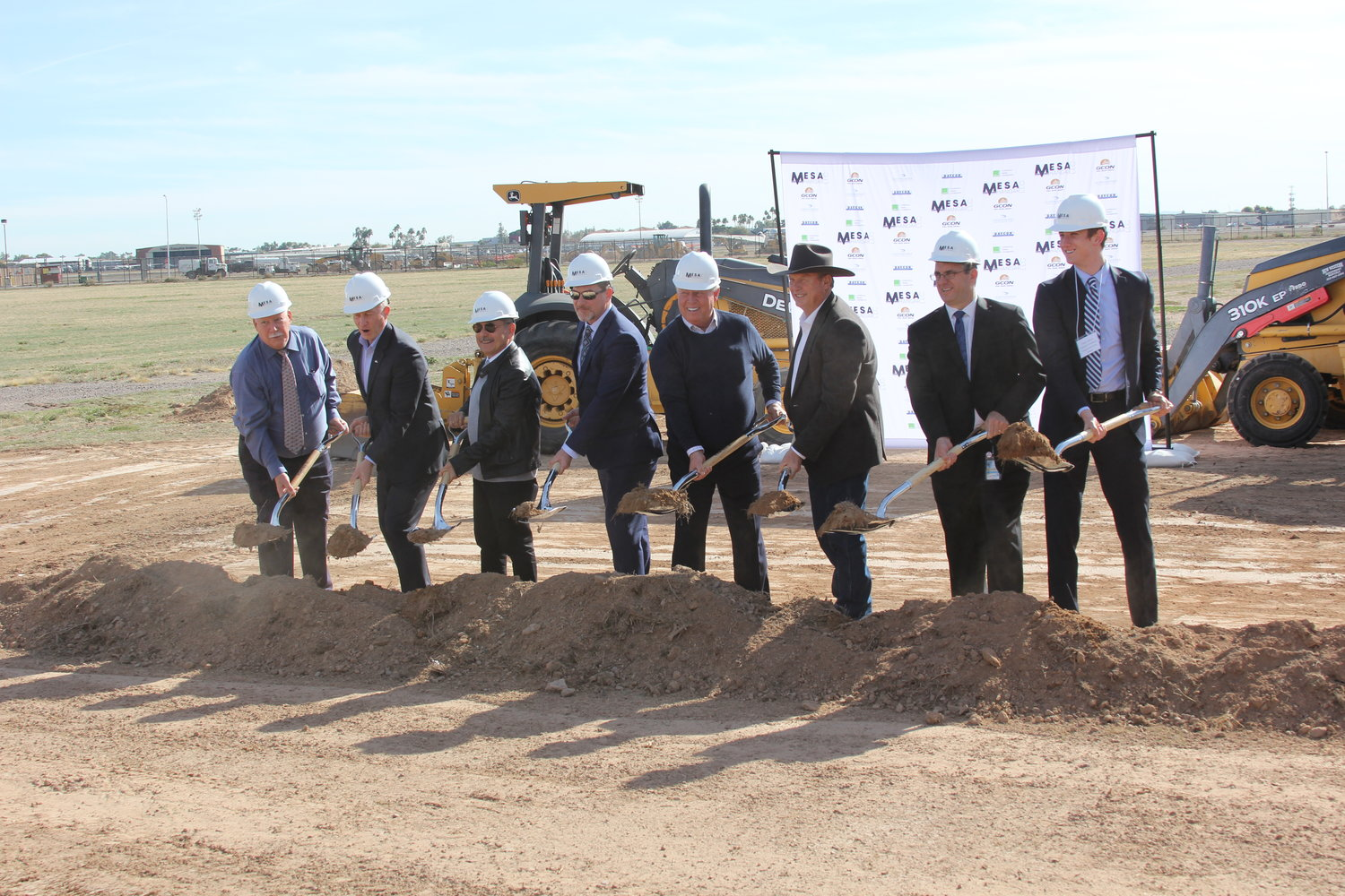 Officials at a groundbreaking ceremony Jan, 14 at the site of a six-building, $65 million project for a new 23-acre development of large aircraft hangars at Falcon Field Airport.