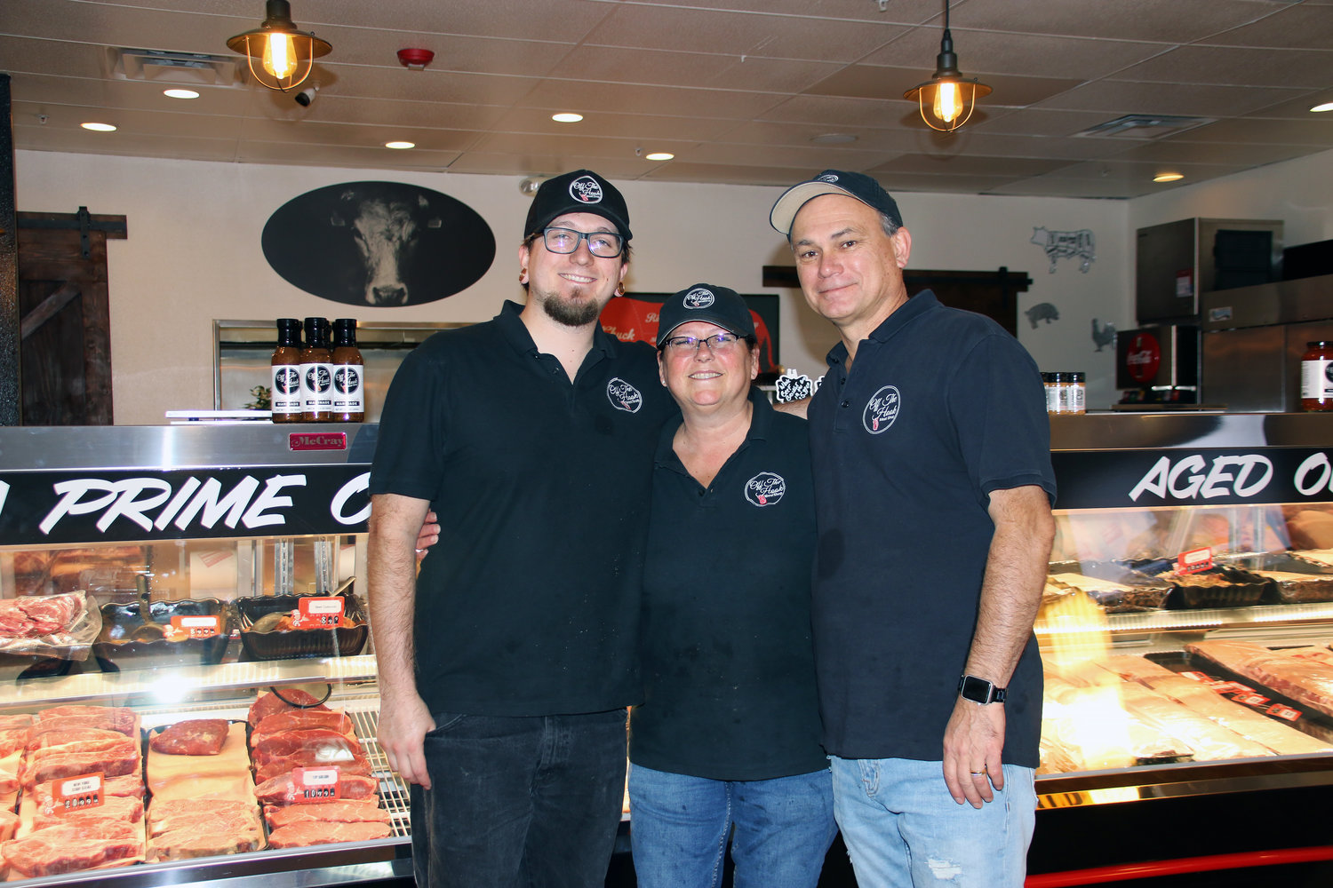 Zachary, left, Christine and Jim Ortega take a break from cutting meat and stocking the display case for a quick family portrait.