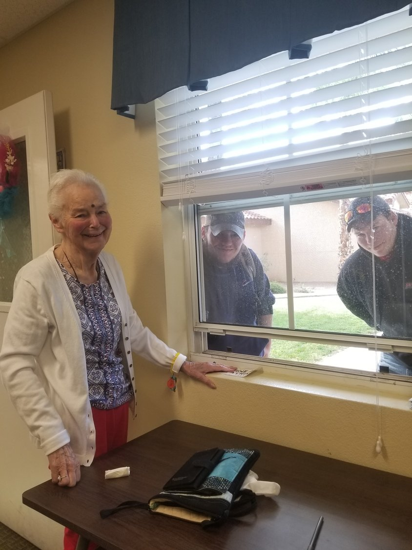 Resident Barbara Mackinaw talking to her grandsons from Duluth, Minnesota, through Marketing Director Cindy Deck's office window.
