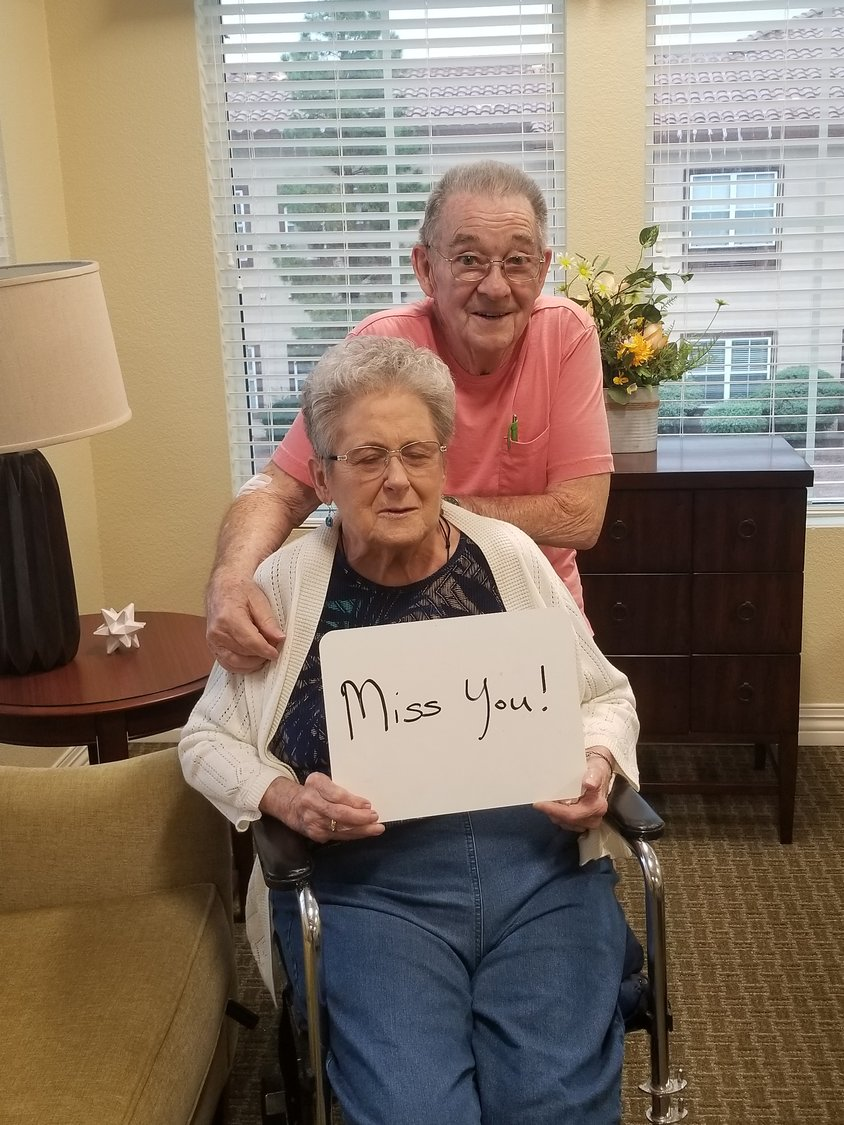"Residents LaVerne and Wayne hug holding a sign to their kids and grandkids saying, ""miss you!"""