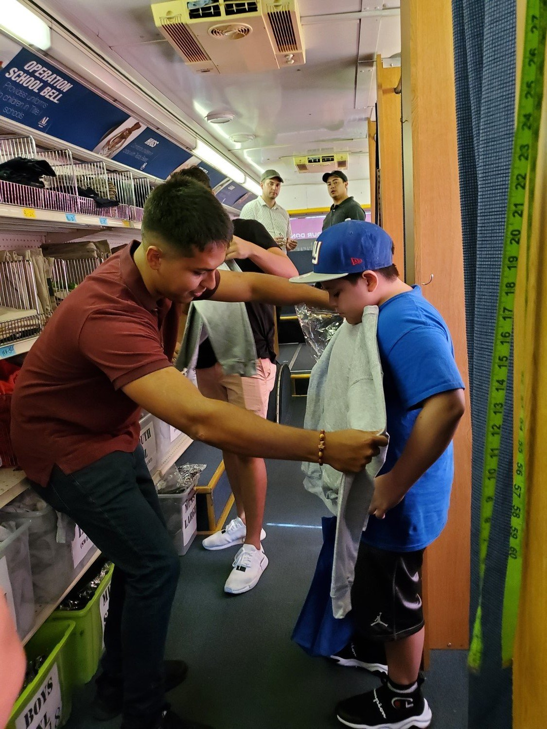 On the Delivering Dream Bus, students work with volunteers to select correct sizes and receive a bundle of items valued at about $200-250.