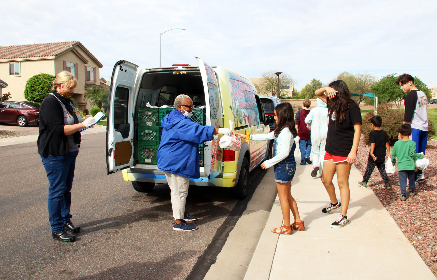 Litchfield Elementary Food Services site supervisor Nichole Tudor, left, and bus driver Jocelyn Zvosechz hand out grab-and-go meals to kids in Avondale's Rio Crossing neighborhood March 25.