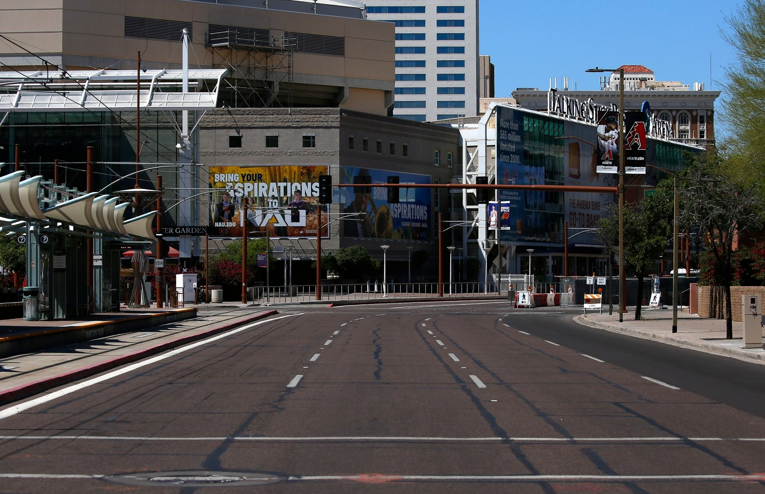 An empty street is devoid of vehicular traffic and pedestrians due to the coronavirus Sunday, March 29, 2020, in Phoenix. The city is closing park amenities for the foreseeable future.