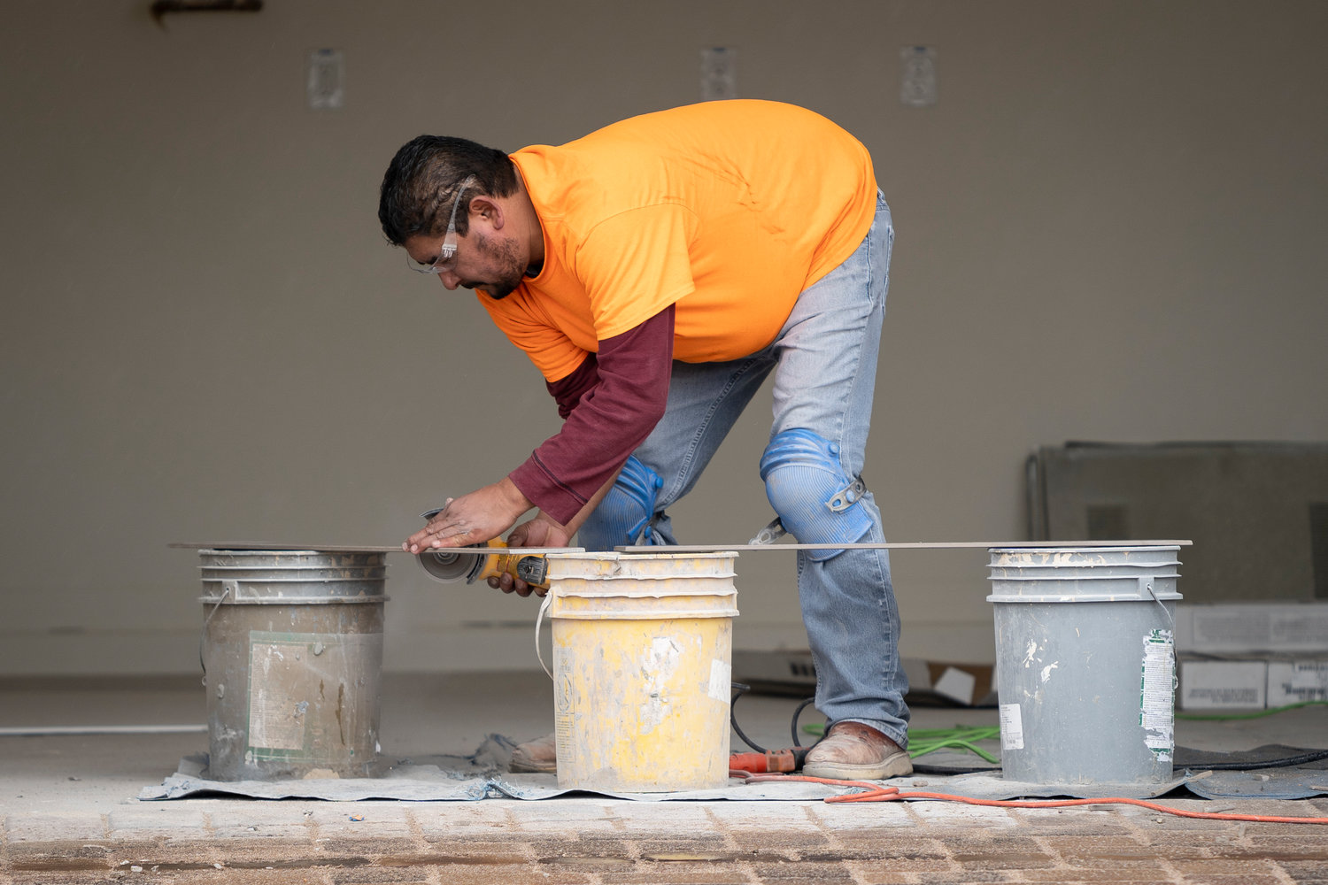 A construction worker cuts tiles at the site of a future home near 91st Avenue and Pinnacle Peak Road Feb. 14 2019 in Peoria.