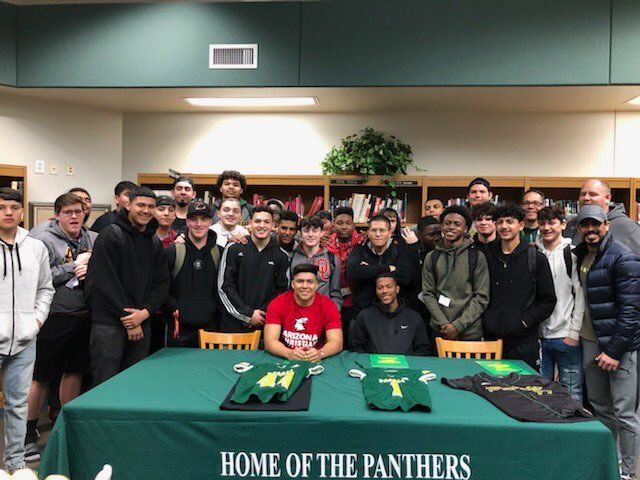 Teammates and friends surround Peoria football seniors Gabriel Ocampo, sitting at left, and Jovon Scott sign with their college football team Feb. 5. They will be rivals in college. Ocampo, a defensive end, signed with Arizona Christian while Scott, a wide receiver, signed with Ottawa Arizona.
