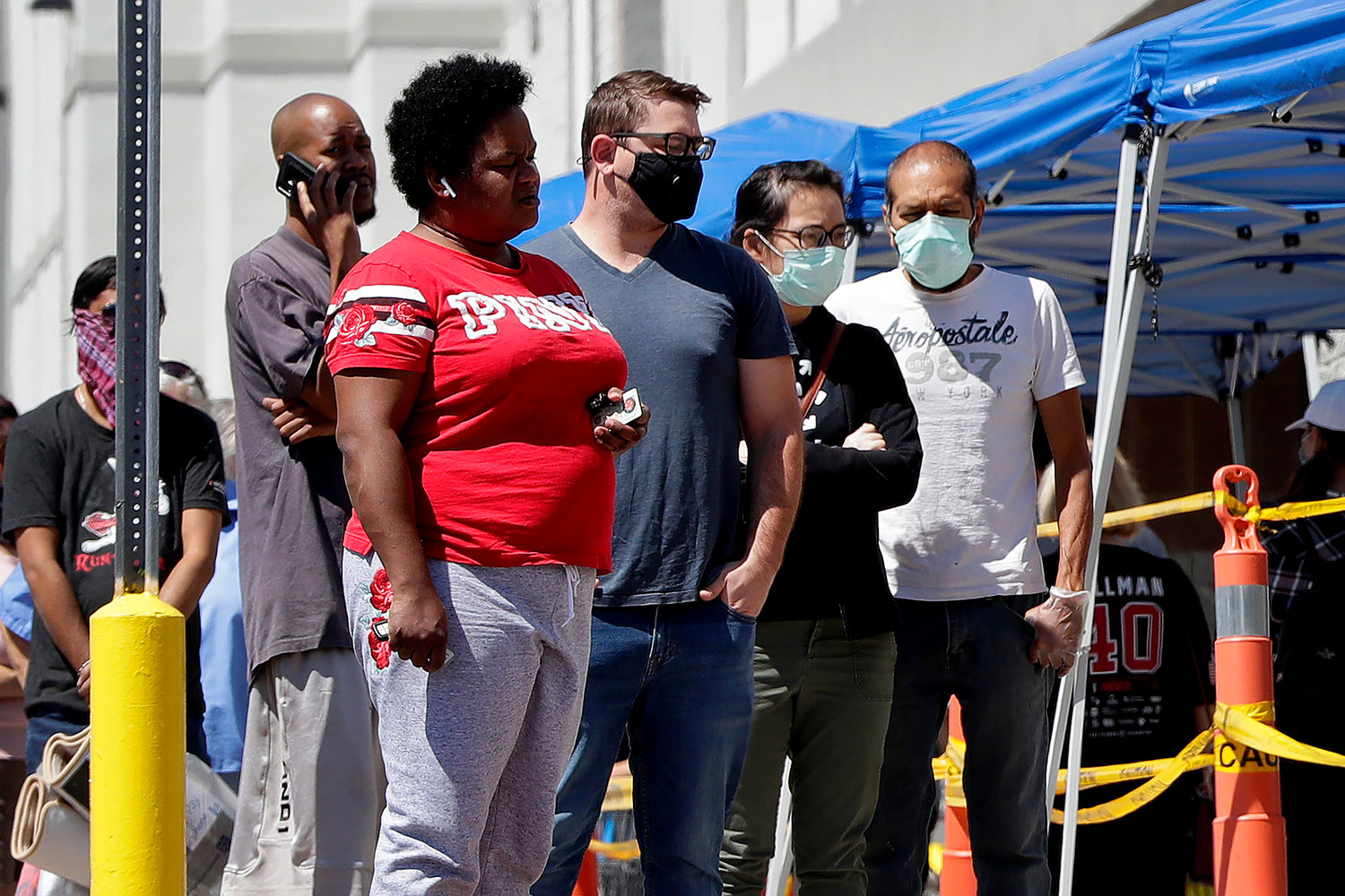Some people wearing face masks wait in line to shop Saturday, April 4, 2020, in Tempe, Arizona.