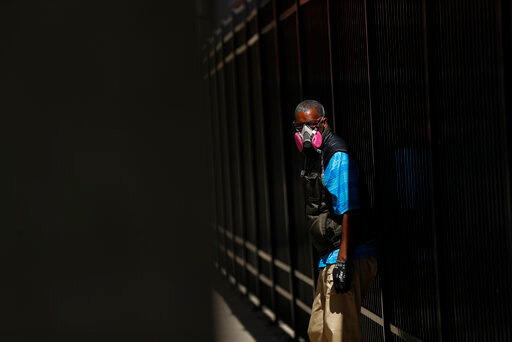 A man wears a protective mask while waiting for a bus in Detroit, Wednesday, April 8, 2020. Detroit buses will have surgical masks available to riders starting Wednesday, a new precaution the city is taking from the new coronavirus COVID-19. (AP Photo/Paul Sancya)