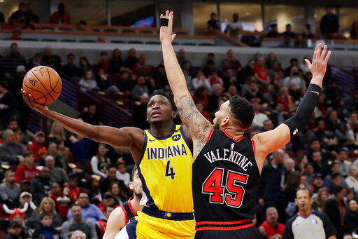 Indiana Pacers guard Victor Oladipo, left, drives to the basket as Chicago Bulls guard Denzel Valentine defends during the first half of an NBA basketball game in Chicago, Friday, March 6, 2020. (AP Photo/Nam Y. Huh)
