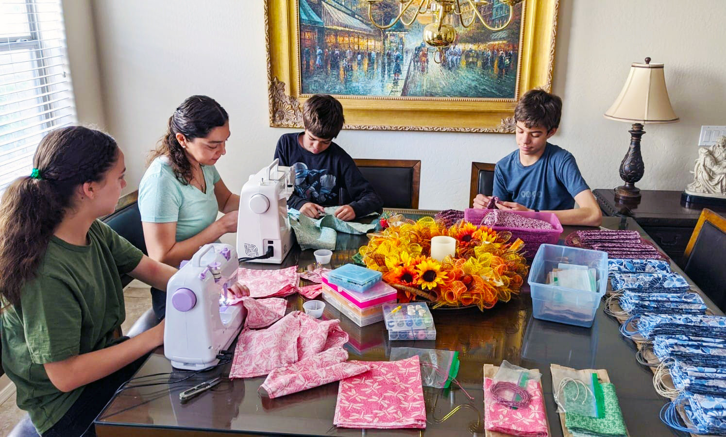 Susy Aleman sews masks with her children, 13-year-old Anna, left, 11-year-old Franco and 15-year-old Leo at their West Valley home.