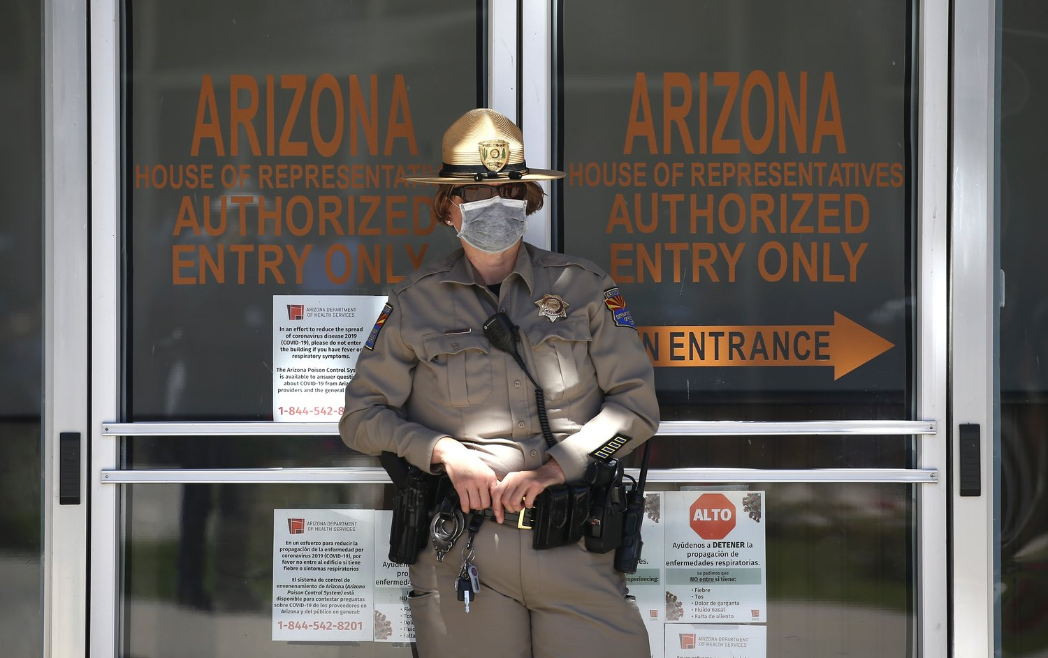 A Department of Public Safety police officer stands in front of the Arizona House of Representatives building as protesters rally at the state Capitol to 're-open' Arizona against the governor's stay-at-home order due to the coronavirus Monday, April 20, 2020, in Phoenix.