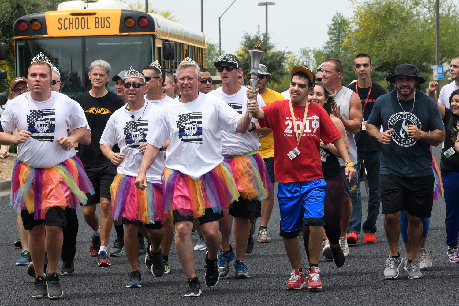 Avondale Police Chief Dale Nannenga carries the torch with a Special Olympian as he and his command staff run the department's leg of the 2019 Law Enforcement Torch Run wearing tutus after APD officers met the chief's T-shirt fundraising challenge.