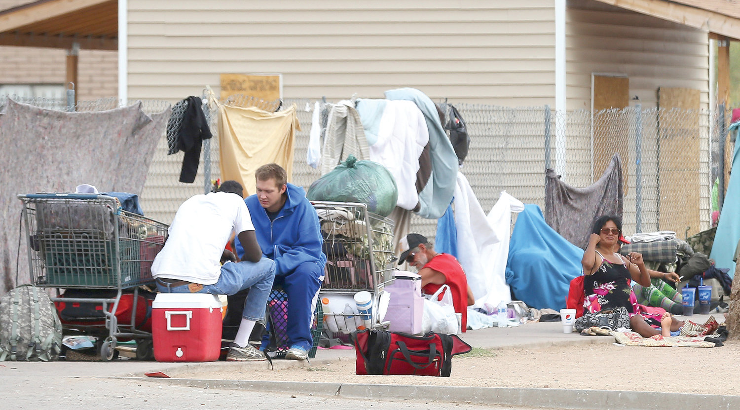 In this May 2, 2019 file photo, homeless people gather on the sidewalk at an encampment in Phoenix. Since 2015, the number of unsheltered homeless people living in the Valley has nearly tripled, according to the most recent count. Meanwhile, government and nonprofit groups are partnering to protect the community during the COVID-19 outbreak.