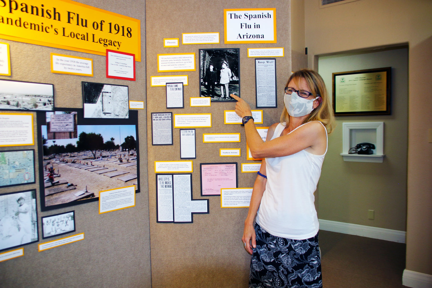 Lisa Hegarty, who curated the Spanish flu pandemic exhibit at the Litchfield Park Historical Society Museum, points to a photo of Arizona Gov. George W.P. Hunt and another man wearing face masks during a 1918 outing in Phoenix.