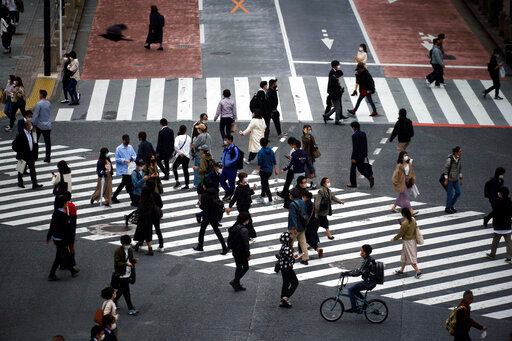 Pedestrians pass a street crossing Friday, May 22, 2020, in Tokyo. Tokyo is still under a coronavirus state of emergency until the end of May though there have been no hard lockdowns. (AP Photo/Eugene Hoshiko)