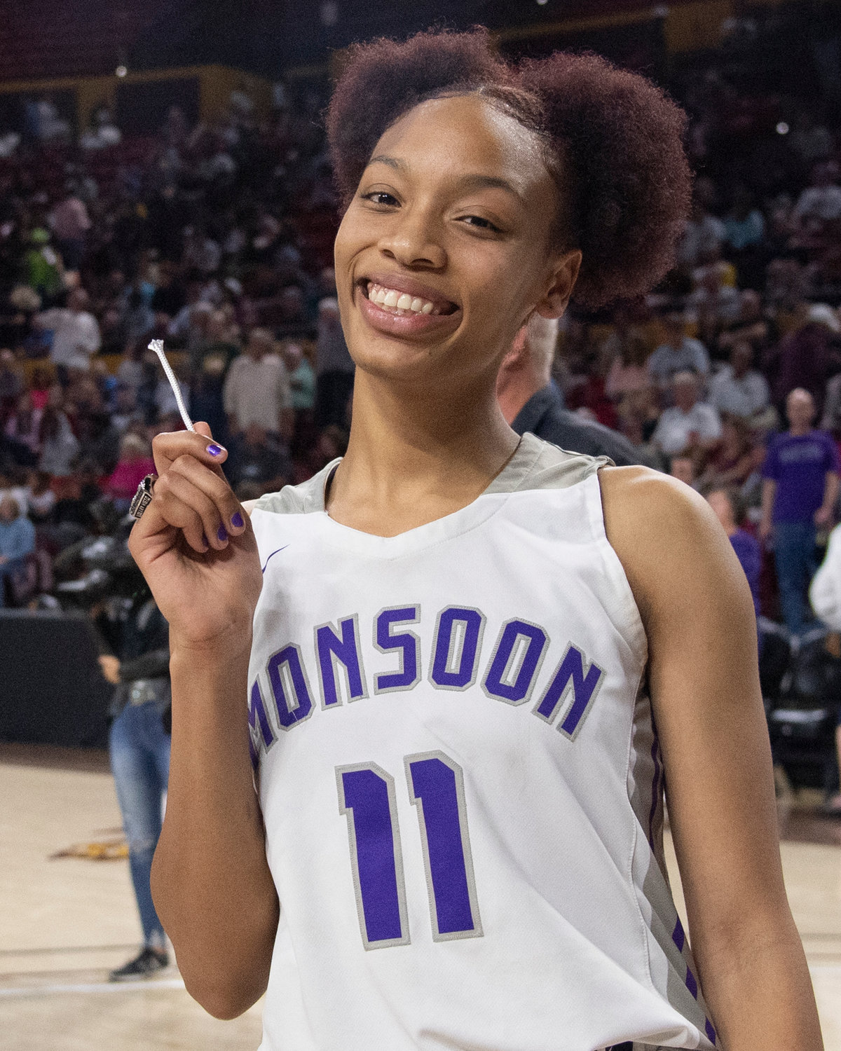 Valley Vista junior Marisa Davis smiles and holds up a strand of the net March 3 after the Monsoon defeated Chandler Hamilton to win the 6A state girls basketball title at Desert Financial Arena in Tempe.