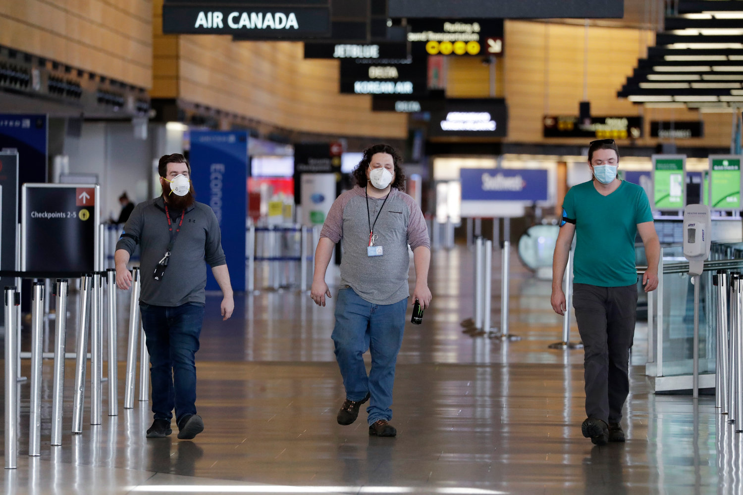 In this photo taken May 18, 2020, workers wear masks on the first day they are required there at Seattle Tacoma International Airport, in SeaTac, Washington.